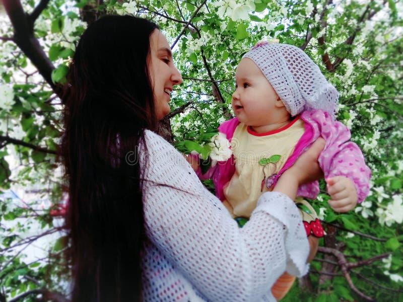 Moder och barn i blommorna av Apple royaltyfri fotografi