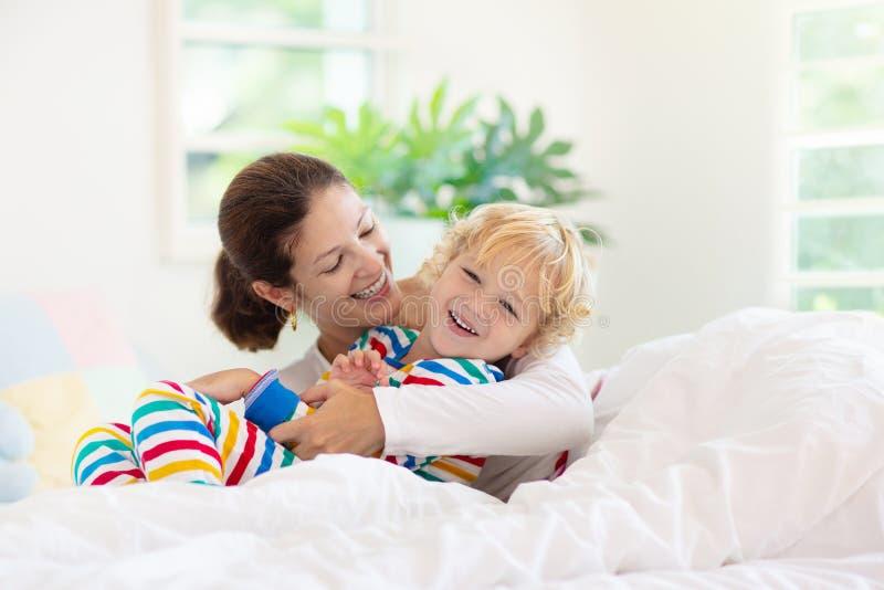 Moder och barn i s?ng Mamman och behandla som ett barn hemma royaltyfria bilder