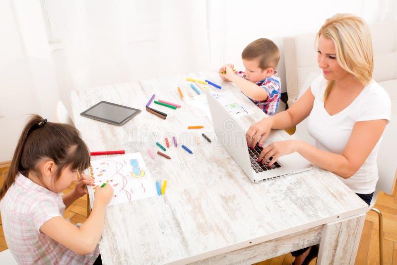 Moder och barn med en hemmastadd bärbar dator arkivfoton