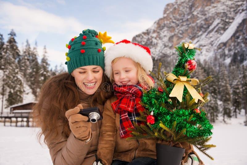 Moder och barn med julgranen som in camera kontrollerar foto royaltyfria foton