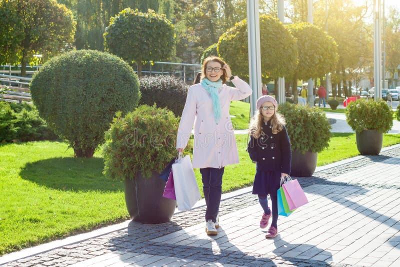 Moder och barn, med shoppingpåsar som promenerar stadsgatan arkivbilder