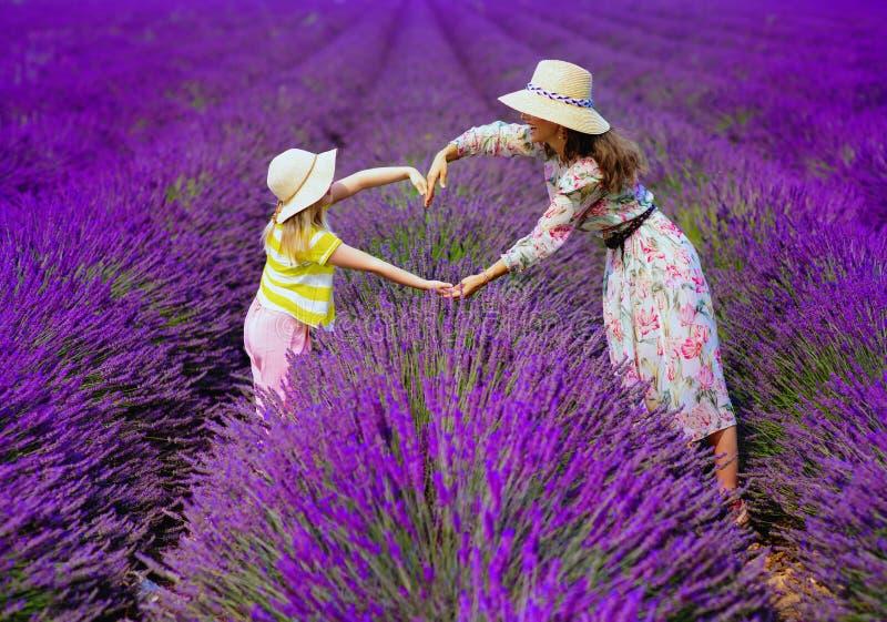 Moder och barn mot lavendelfältet som gör hjärta med händer arkivfoto