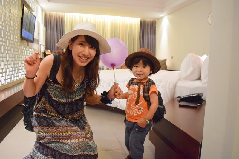 moder och barn på avslappnande hotellrum arkivbild