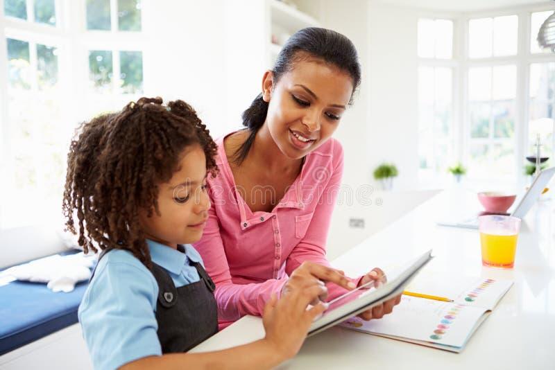 Moder och barn som använder den Digital minnestavlan för läxa