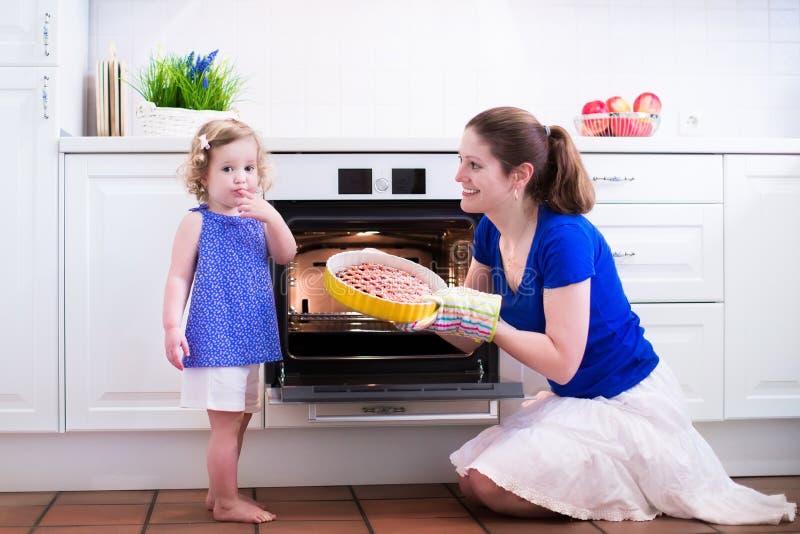 Moder och barn som bakar en kaka royaltyfria bilder