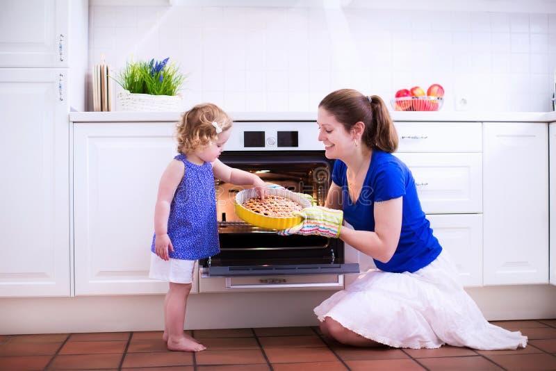 Moder och barn som bakar en kaka royaltyfria foton
