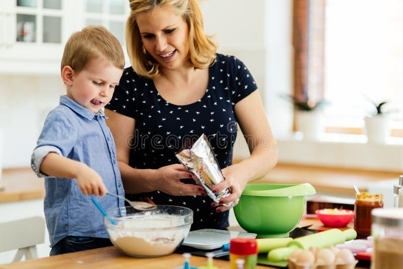 Moder och barn som förbereder kakor arkivbild
