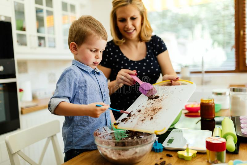 Moder och barn som förbereder kakor i kök royaltyfri foto