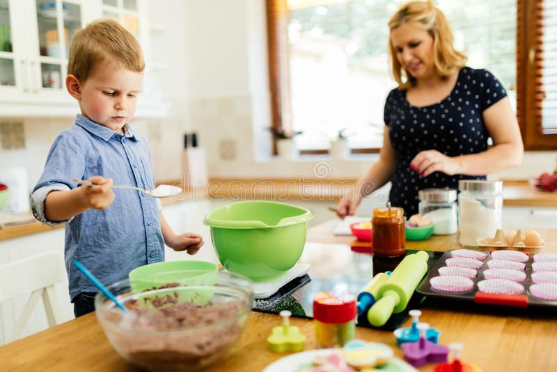 Moder och barn som förbereder kakor i kök royaltyfri fotografi