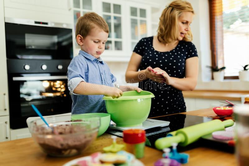 Moder och barn som förbereder kakor i kök arkivbild