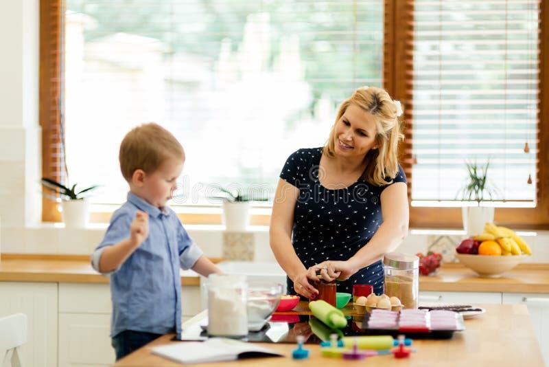Moder och barn som förbereder kakor i kök arkivbilder