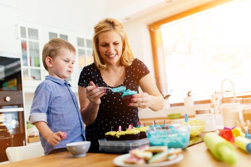 Moder och barn som förbereder kakor i kök arkivfoto