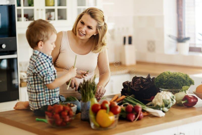 Moder och barn som förbereder lunch arkivbild