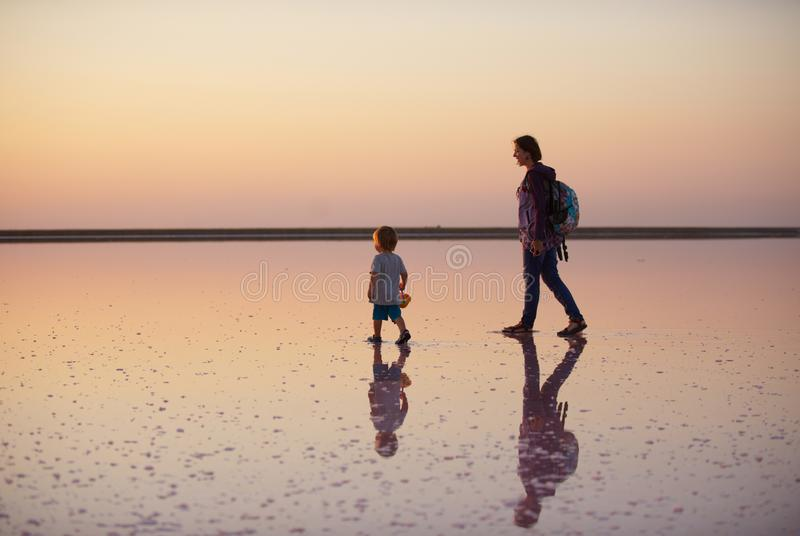 Moder och barn som går på ett salt och en saltvatten av en rosa sjö som färgas av den microalgaeDunaliella salinaen arkivfoton