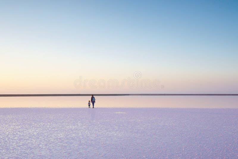 Moder och barn som går på ett salt och en saltvatten av en rosa sjö som färgas av den microalgaeDunaliella salinaen royaltyfri fotografi