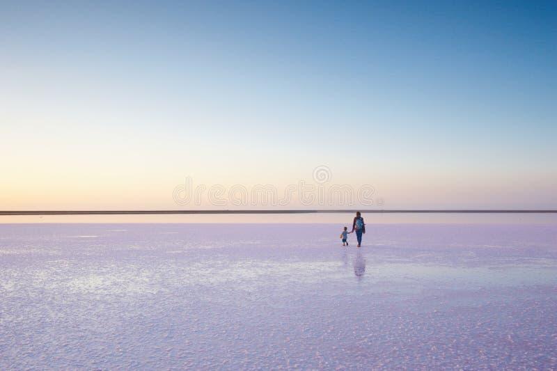 Moder och barn som går på ett salt och en saltvatten av en rosa sjö som färgas av den microalgaeDunaliella salinaen royaltyfri foto