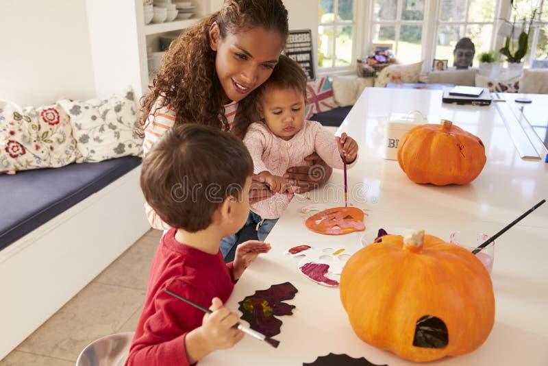 Moder och barn som gör allhelgonaaftongarneringar hemmastadda royaltyfria foton