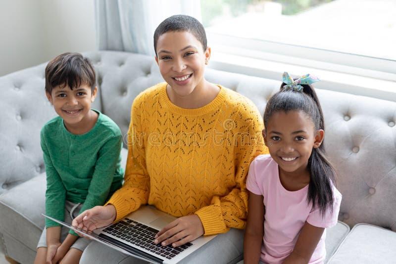 Moder och barn som hemma använder bärbara datorn på en soffa i vardagsrum arkivbilder