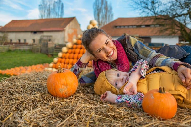 Moder och barn som lägger på höstack med pumpor arkivbild