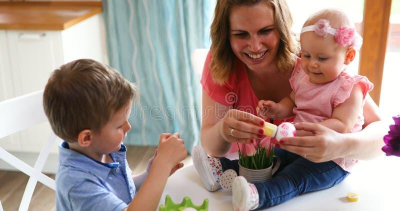 Moder och barn som målar färgrika ägg royaltyfri fotografi