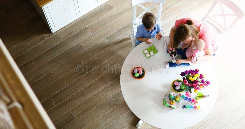 Moder och barn som målar färgrika ägg arkivfoto