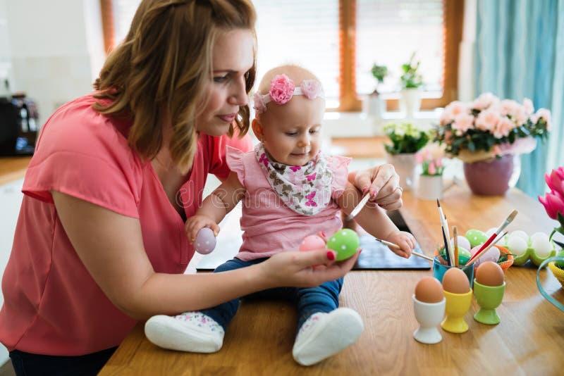 Moder och barn som målar färgrika ägg royaltyfri bild