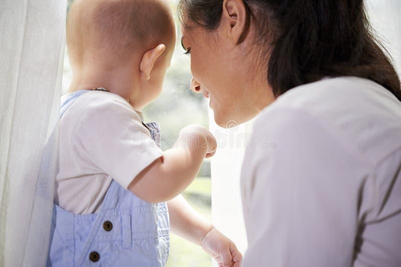Moder och barn som ser till och med f?nster arkivfoto