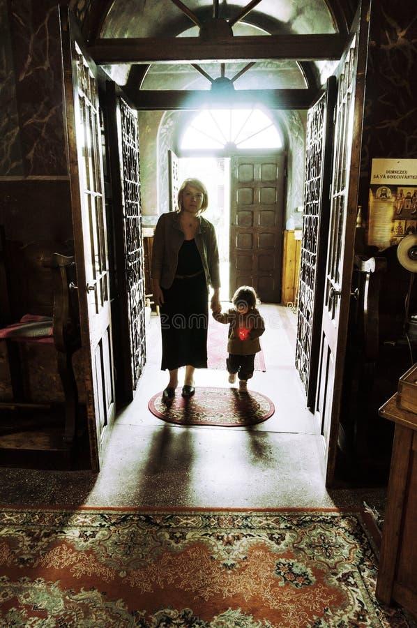 Moder och barn som skriver in i en kyrka royaltyfria bilder