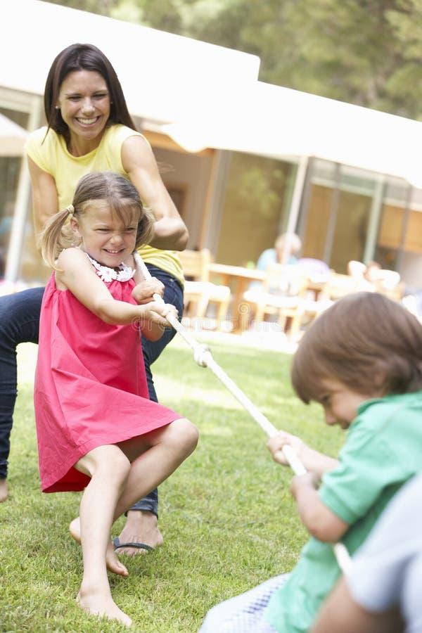Moder och barn som spelar dragkampen fotografering för bildbyråer