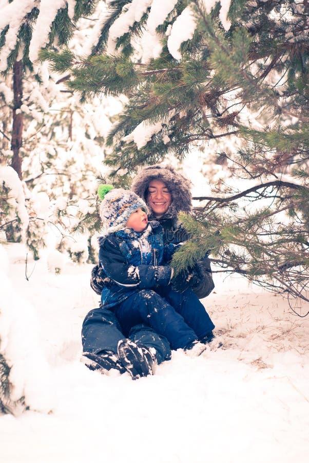 Moder och barn som spelar i vinter royaltyfri bild