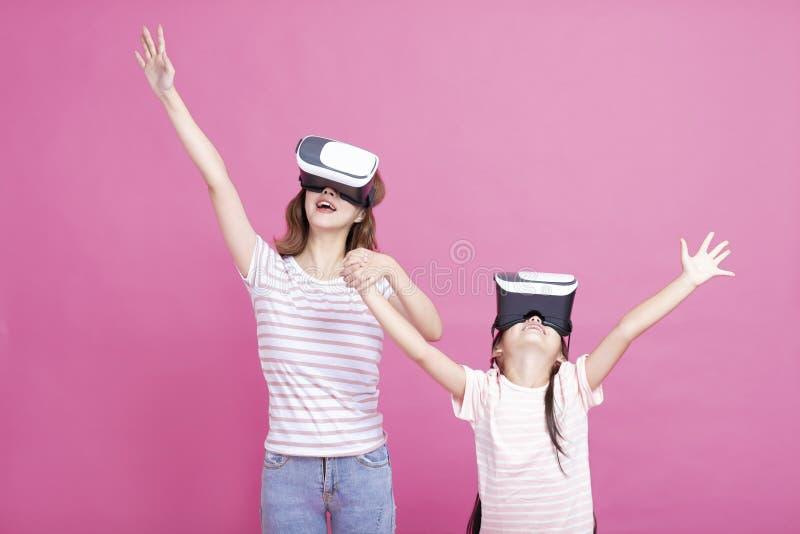 Moder och barn som spelar samman med virtuell verkligheth?rlurar med mikrofon arkivfoton