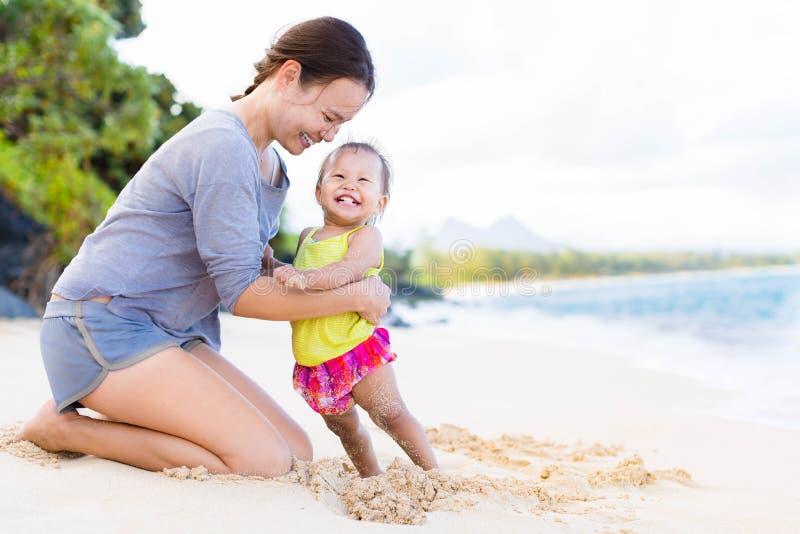 Moder och barn som spelar och skrattar på strandkust arkivbild