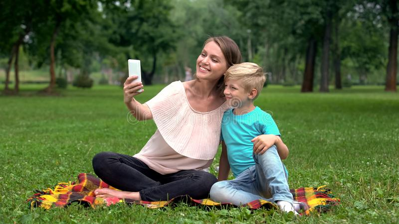 Moder och barn som tar selfie med smartphonen som tillsammans tycker om familjhelg royaltyfria bilder