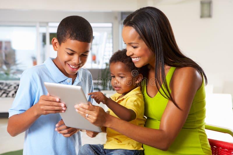 Moder och barn som tillsammans använder den Digital minnestavlan i kök arkivbilder