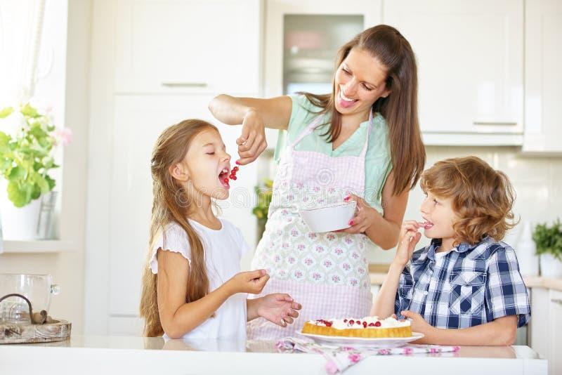 Moder och barn som tillsammans bakar kakan arkivfoto