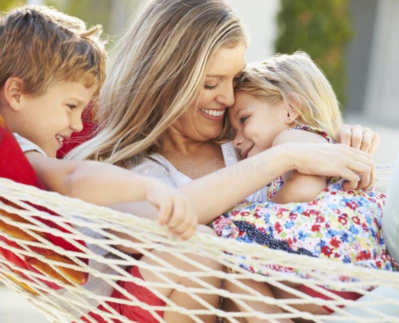 Moder och barn som tillsammans kopplar av i trädgårds- hängmatta royaltyfria bilder