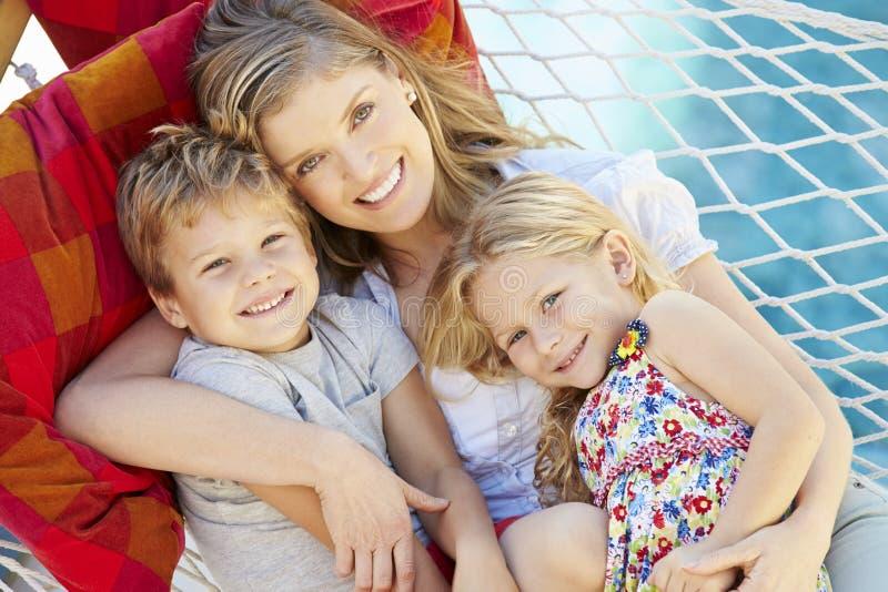 Moder och barn som tillsammans kopplar av i trädgårds- hängmatta royaltyfri foto