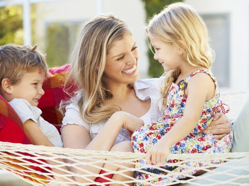 Moder och barn som tillsammans kopplar av i trädgårds- hängmatta royaltyfri fotografi