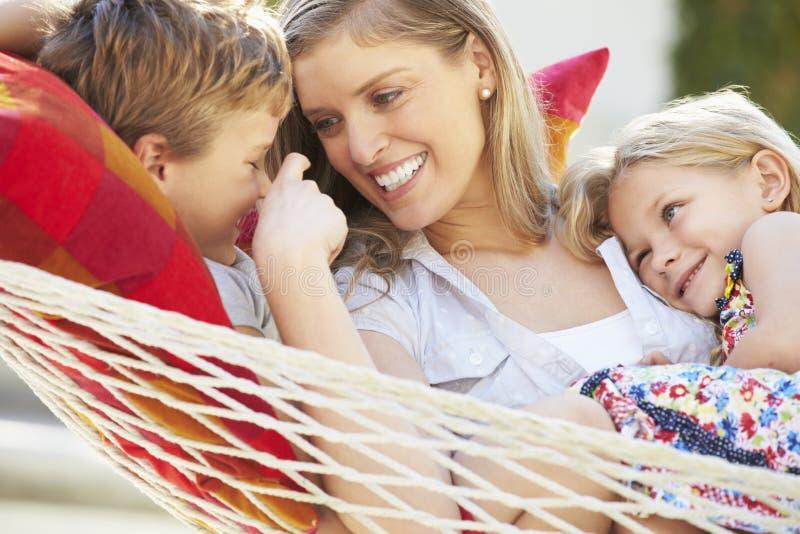 Moder och barn som tillsammans kopplar av i trädgårds- hängmatta arkivfoton