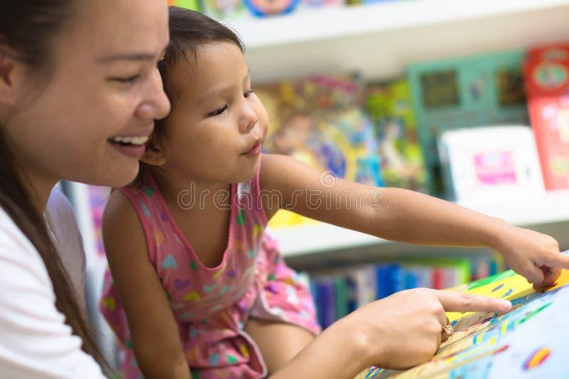 Moder och barn som tillsammans ser bilderböcker Familj Tid royaltyfria foton