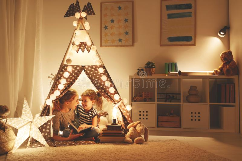 Moder- och barndotter som för läser en bok och en ficklampa arkivfoto