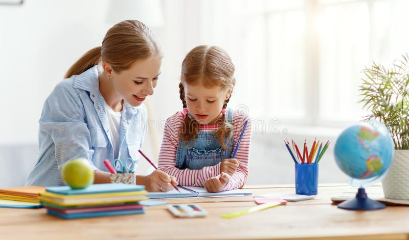 Moder- och barndotter som hemma g?r l?xahandstil och l?sning royaltyfria bilder