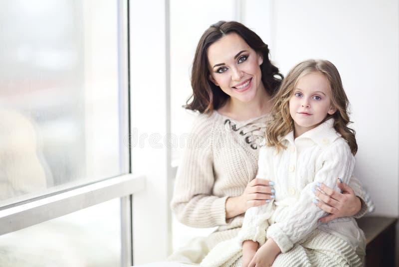 Moder- och barndotter som kramar av fönstret som bär hemtrevliga tröjor royaltyfria bilder