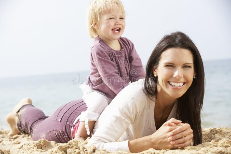 Moder- och barndottersammanträde på stranden tillsammans arkivbilder