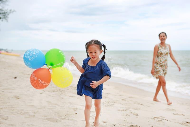 Moder- och barnflicka på stranden med färgrika ballonger Den lyckliga mannen tycker om p? ferier p? havet royaltyfri bild