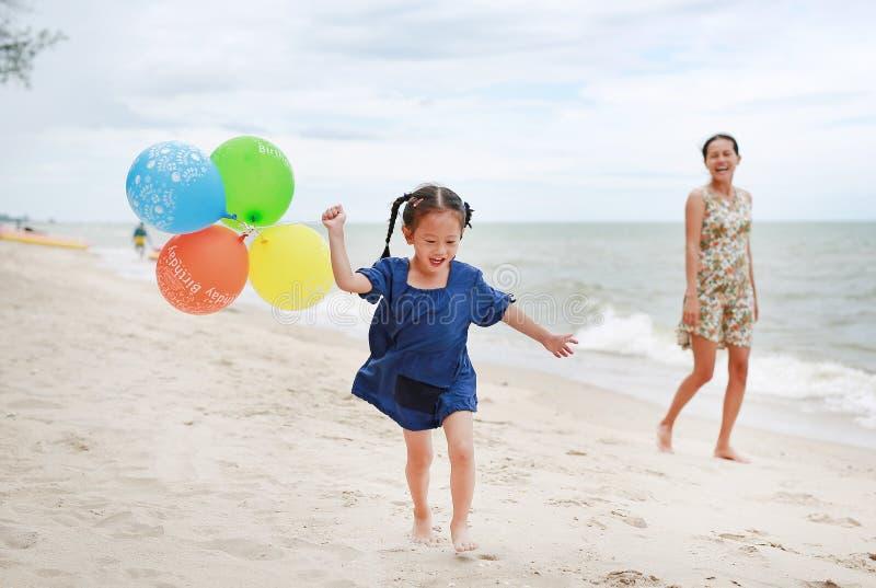 Moder- och barnflicka p? stranden med f?rgrika ballonger Den lyckliga mannen tycker om p? ferier p? havet fotografering för bildbyråer