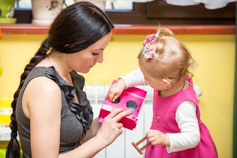 Moder- och barnflicka som spelar i dagis i Montessori grupp royaltyfria foton