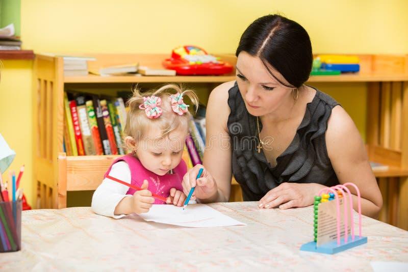 Moder- och barnflicka som spelar i dagis i Montessori grupp royaltyfri foto