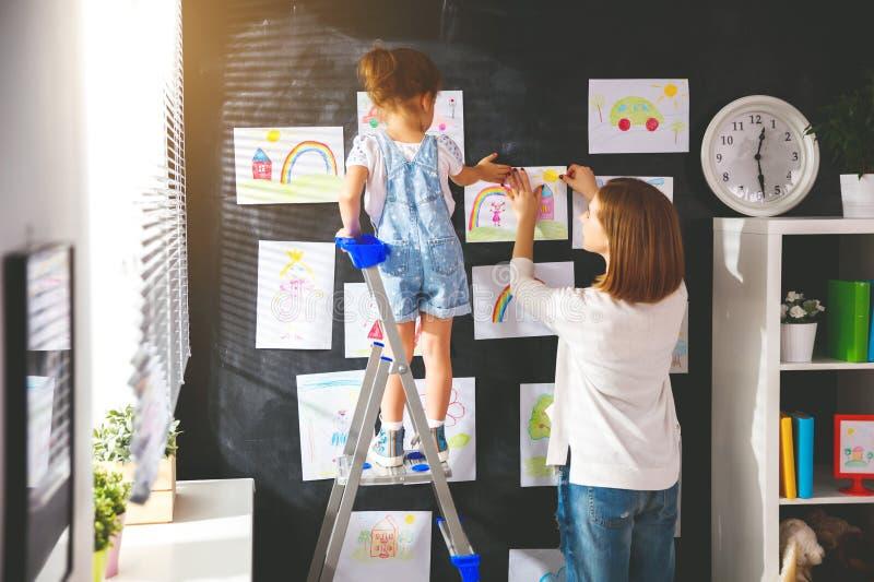 Moder- och barnflickan hänger deras teckningar på väggen royaltyfria foton