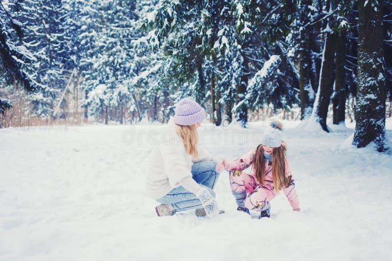 Moder- och barnflickan på snöig vinter går i natur royaltyfri fotografi